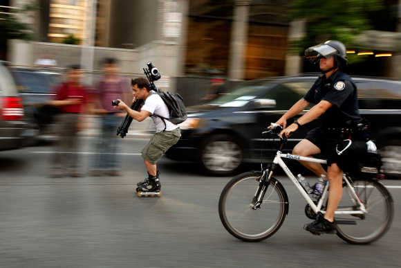 A man on rollerblades carrying cameras rolls along with bicycle police in Toronto.