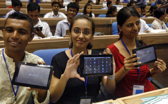 Students display Aakash at its launch ceremony in New Delhi.