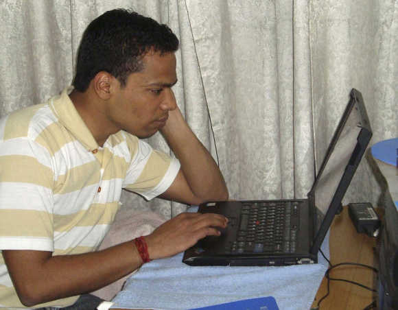 Abhishek Chaudhary, a B-School student, works on his laptop inside his house in New Delhi.