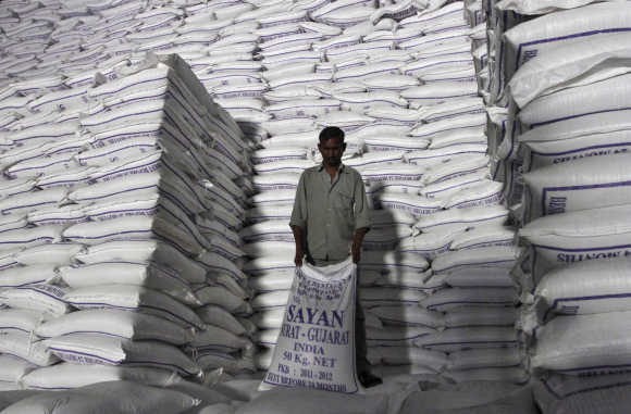 A worker shifts a sack of sugar at a godown inside a sugar factory at Sanyan village in Gujarat.