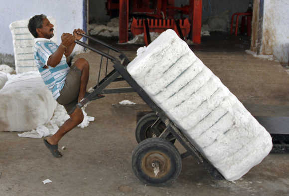 A labourer pulls down a handcart after loading a bundle of processed cotton at a processing unit.
