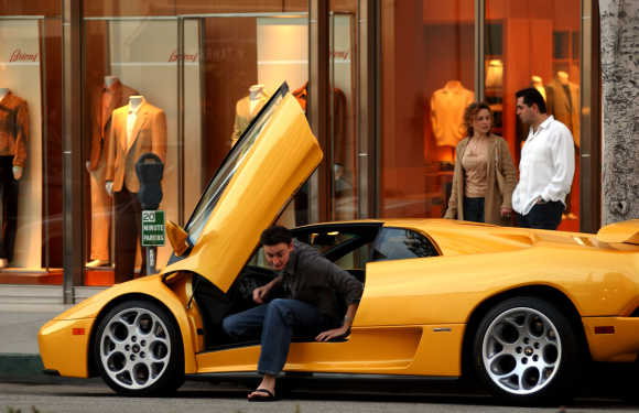 The driver of a Lamborghini sports car parks on Rodeo Drive in Hollywood.