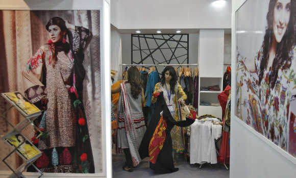 Exhibitors from Pakistan prepare their stall of clothing at the Lifestyle Pakistan Exhibition in New Delhi.