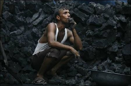 A labourer smokes a bidi, as he takes rest between unloading coal from a supply truck in Noida.