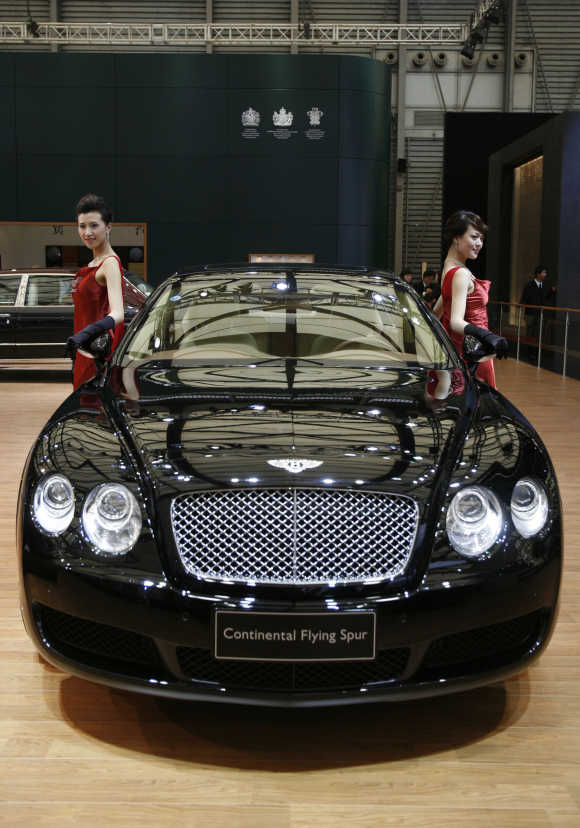 Models pose beside a Bentley Continental Flying Spur in Shanghai, China.