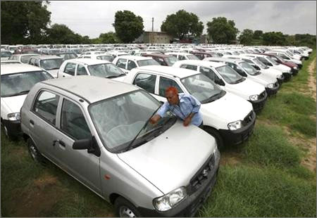A worker adjusts the windscreen wipers of a parked Alto car at a Maruti Suzuki stockyard on the outskirts of Ahmedabad.