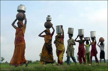 People carry pots containing water on their heads on the outskirts of Mathura.