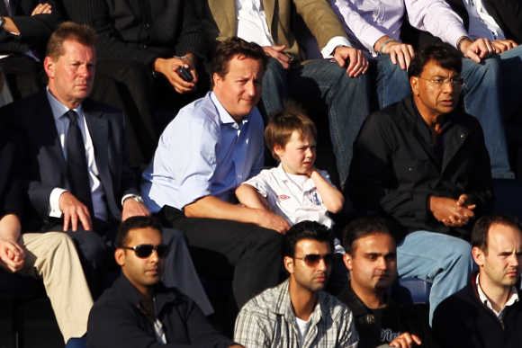 British Prime Minister David Cameron, his son Arthur and Lakshmi Mittal watch the Barclays Premier League match between Queens Park Rangers and Aston Villa at Loftus Road in London, England.