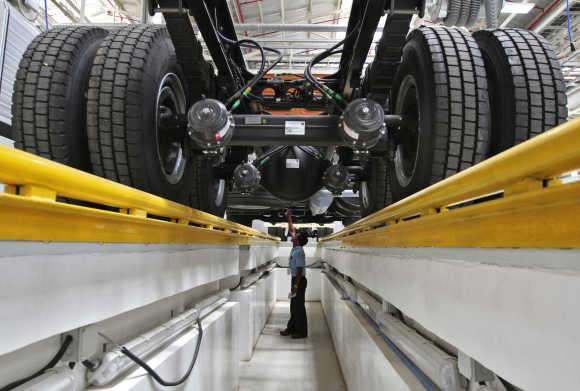 An employee inspects the engine of a BharatBenz truck inside Daimler's new factory in Oragadam in the Kancheepuram district of Tamil Nadu.