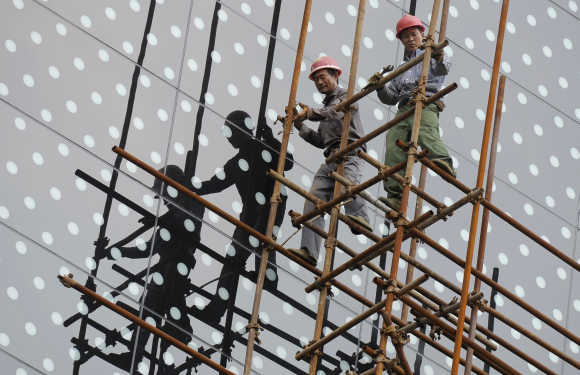 Labourers cast their shadows on the glass facade of a hotel as they take down scaffolding at a construction site in Nanjing, China.