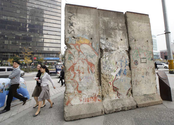 People walk past a section of the Berlin Wall displayed at Berlin Plaza in central Seoul.