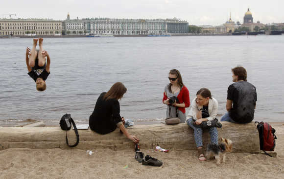 People enjoy a warm day on the banks of the Neva River in central St Petersburg.