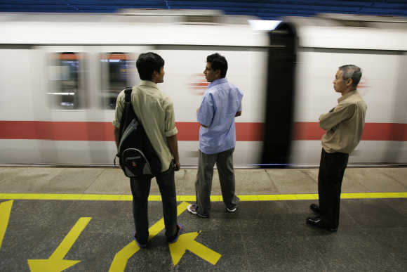 Commuters wait to board an MRT train at a station in Singapore.