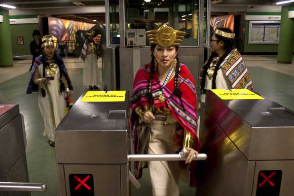 A dancer from a Peruvian folkloric group passes through a turnstile at a subway station in Santiago.