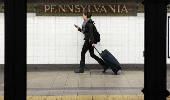 A woman wheels luggage along the subway platform at the 34th Street Penn Station stop in New York.