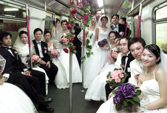 Couples pose for photographers in a subway train during a mass wedding in Hong Kong.