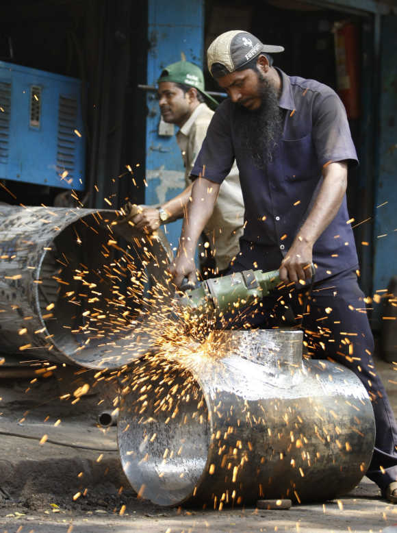 A worker uses an angle grinder at a small steel workshop in Mumbai.