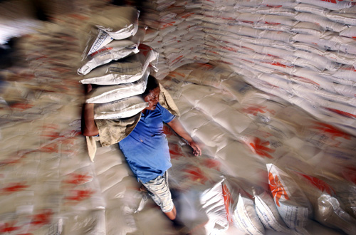 worker carries sacks of rice at a warehouse owned by Indonesia's state procurement agency Bulog in Makassar.