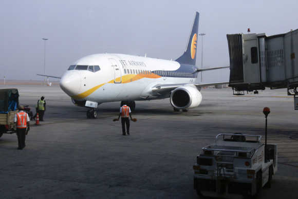Ground staff guide a Jet Airways aircraft towards a gate on the tarmac at Bangalore International Airport.