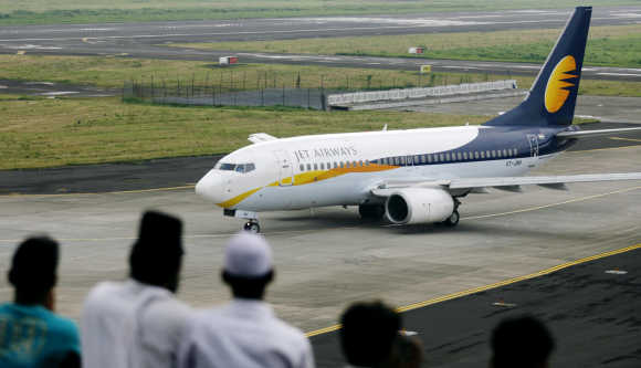 People look at a Jet Airways aircraft preparing to take-off in Mumbai.