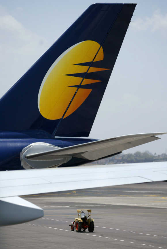 A vehicle passes by a Jet Airways aircraft at Mumbai airport.