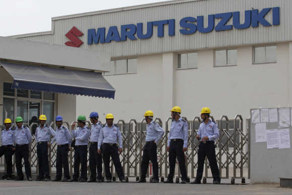 Private security guards stand outside the main entrance to the Maruti Suzuki plant where workers are striking in Manesar, Haryana.