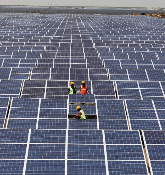 Workers install photovoltaic solar panels at the Gujarat solar park in Charanka.