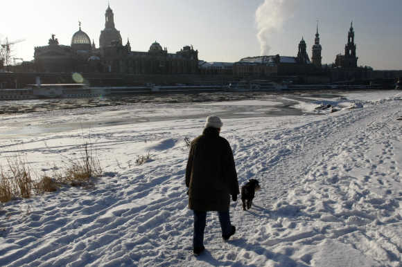 A women and her dog walks along the frozen river bank in front of the old city at river Elbe in Dresden