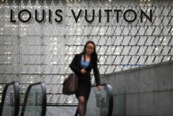 A woman walks by a Louis Vuitton luxury boutique at the IFC Mall in Shanghai.