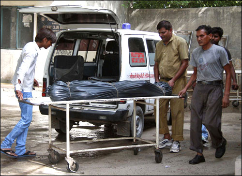 Hospital staff move the covered body of Awanish Kumar Dev, human resources manager at Maruti Suzuki.