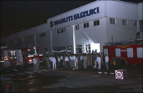 Police and firefighters are seen at the Maruti Suzuki's plant after the clash.