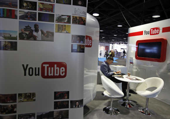 A visitor sits at the YouTube stand during the International Record Music Publishing and Video Music Market in Cannes.