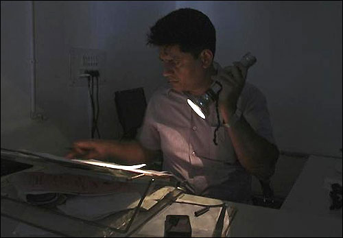 An officer reads documents with the help of a torch at the driving registration and license authority office during a power-cut in Chandigarh, July 31, 2012.