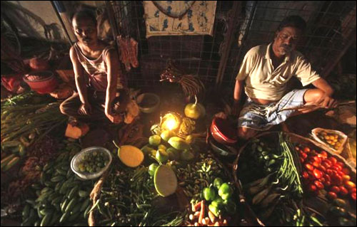 Vegetable vendors wait for customers at their stall during a power-cut in Kolkata.