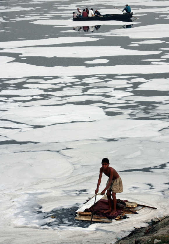 A boy looks for recyclable items in the polluted waters of the Yamuna river in New Delhi.