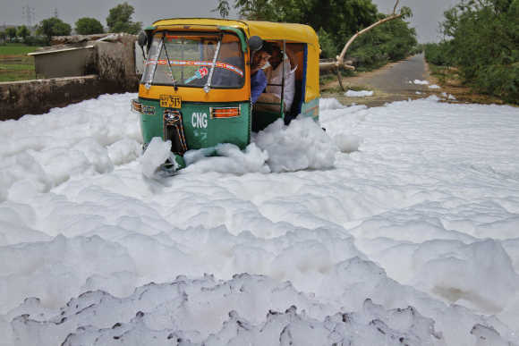 A man looks out of his auto rickshaw as he drives through foam overflowing from a drain outside a factory in Ahmedabad.