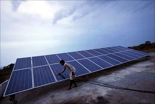 A man cleans panels installed at a solar plant at Meerwada village of Guna district in the central Indian state of Madhya Pradesh.