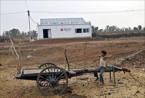 A boy sits on a cart in front of a solar power plant at Meerwada village of Guna district in Madhya Pradesh.