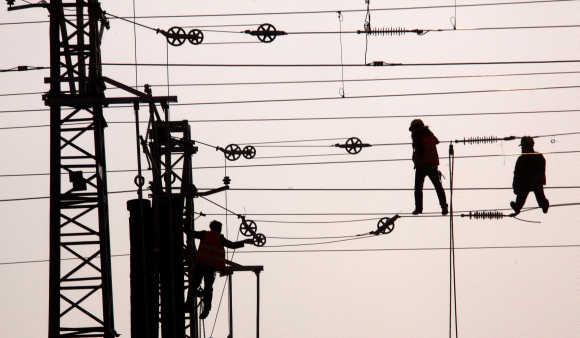 Workmen hang from the power lines for a railway line on the outskirts of Beijing.
