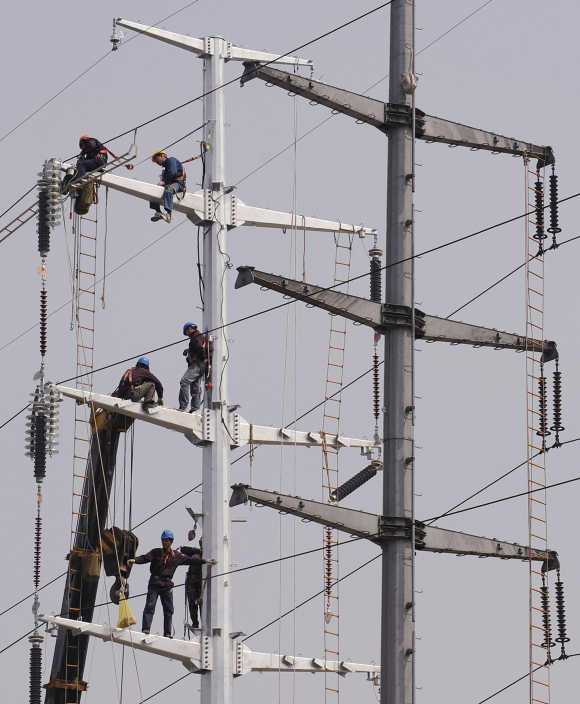 Labourers install electronic cables on power poles in Hefei, China.