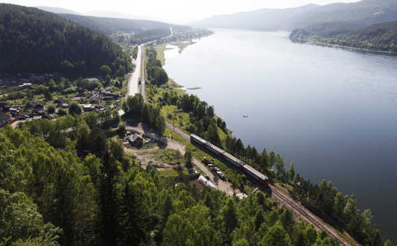 A passenger train moves along a railway along the banks of the Yenisei River near the village of Sliznevo, outside Krasnoyarsk, Russia.