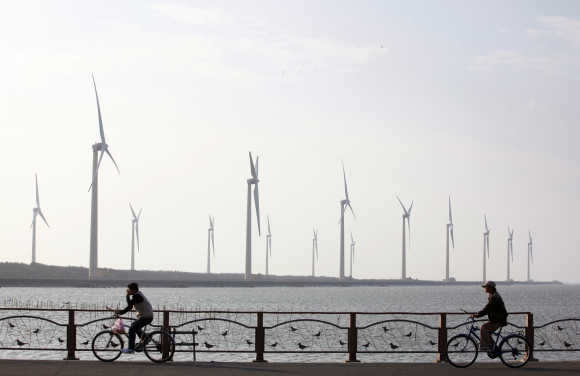 People ride their bicycles in front of wind turbines that generate electricity in Gaomei Wetland in Taichung, Taiwan.