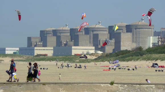 Kites fly in the sky as the Gravelines nuclear power plant is seen across the beach in Petit Fort Philippe, northern France.