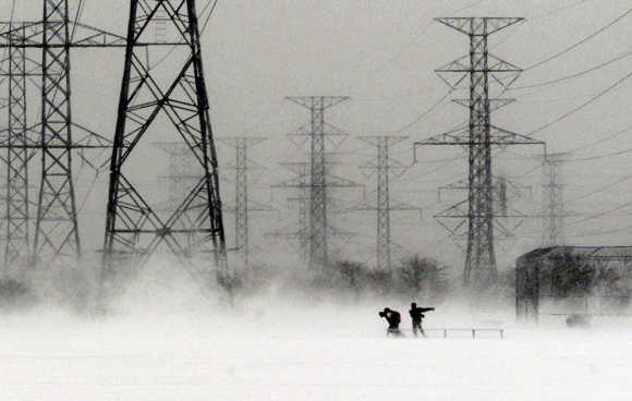 Students, walking to school, are dwarfed by power towers as they fight their way across an open field, during a winter storm, in Pickering east of Toronto.