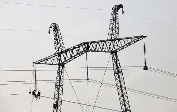 Mechanics work on an electricity pylon in the steppe area near the village of Solyonoozyornoye in Russia's Khakassia region.