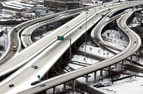 Cars travel on an almost deserted snow covered downtown highway after an overnight storm dropped five inches of snow in Dallas, Texas.