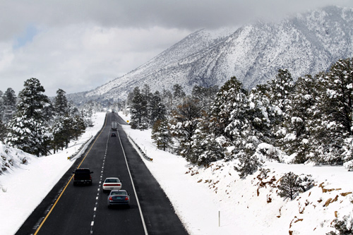 Motorists travel westbound along Interstate 40 after several inches of snow fell during a winter storm in Flagstaff, Arizona.