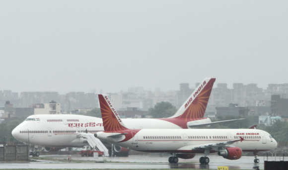 Air India aircrafts stand on the tarmac during heavy rains at the Indira Gandhi International Airport in New Delhi.