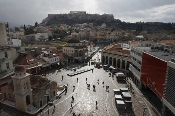 People walk on the Monastiraki square as the Acropolis hill is seen in the background in central Athens.