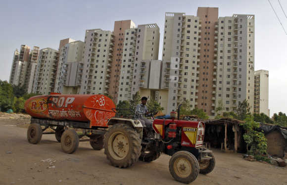 A water tanker moves past Malibu Towne residential apartments in Gurgaon.